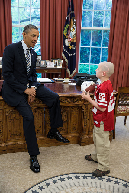 President Barack Obama greets Jack Hoffman, 7, of Atkinson, Neb., in the Oval Office, April 29, 2013. Hoffman, who is battling pediatric brain cancer, gained national attention after he ran for a 69-yard touchdown during a Nebraska Cornhuskers spring football game. Hoffman holds a football that the President signed for him. (Official White House Photo by Pete Souza)