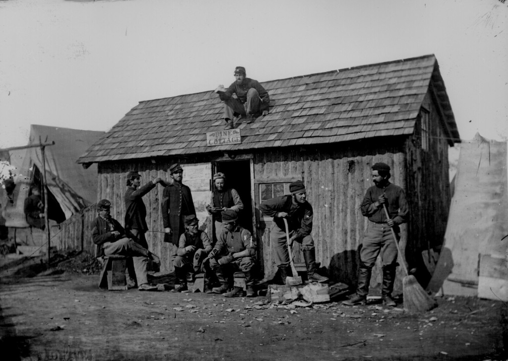 """Winter quarters; soldiers in front of their wooden hut, """"Pine Cottage."""""""