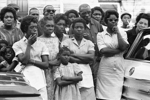 Unidentified mourners, who overflowed the church, stand across the street during funeral services for 14-year-old Carol Robertson, Sept. 17, 1963, Birmingham, Ala. The girl was one of four young African Americans killed in a bomb blast the previous Sunday. (AP)/Via, The Daily Beast