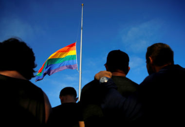 Mourners gather under an LGBT pride flag flying at half-mast for a candlelight vigil in remembrance for mass shooting victims in Orlando, from San Diego, California, U.S. June 12, 2016.  REUTERS/Mike Blake - RTX2FVBC